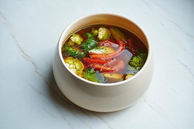Diät hühnersuppe mit viel frischem gemüse - brokkoli, blumenkohl, tomaten in einer weißen keramikschale auf einer marmoroberfläche. diätbrühe