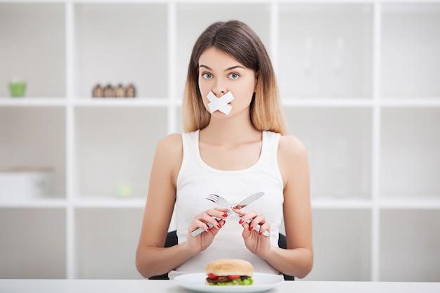 Diät. junge frau mit klebeband über ihrem mund, sie verhindernd, ungesunde fertigkost zu essen.
