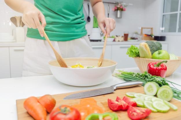 Diät. junge hübsche frau im grünen hemd, das zu hause den gemüsesalat in der schüssel für gutes gesundes in der modernen küche steht und zubereitet