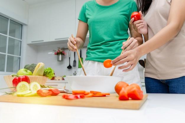 Diät. junge hübsche frau zwei im grünen hemd, das den gemüsesalat steht und zubereitet