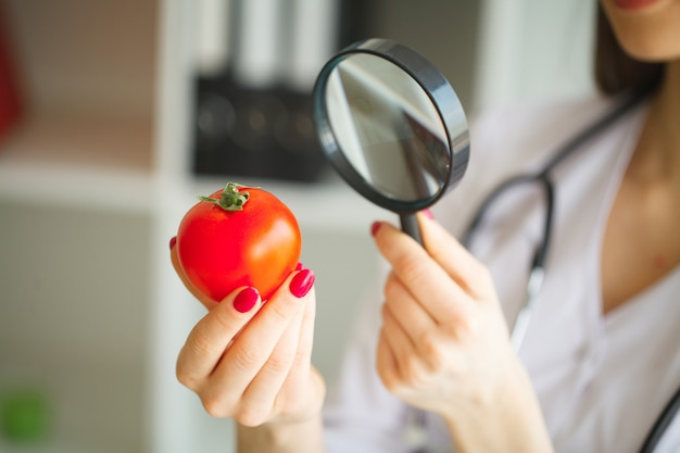 Diät-konzept. diätetiker, der gemüse mit lupe kontrolliert