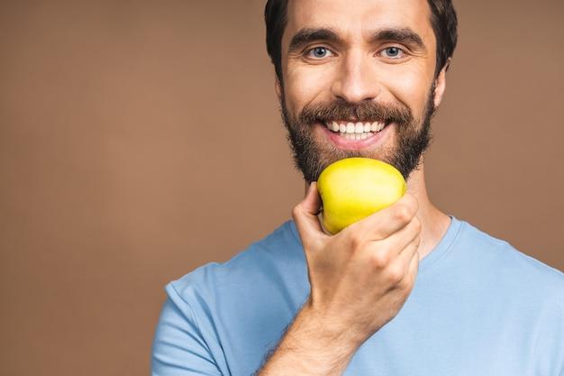 Diät-konzept. fröhlicher schöner bärtiger junger mann, der grünen apfel isst, lokalisiert über beigem hintergrund.