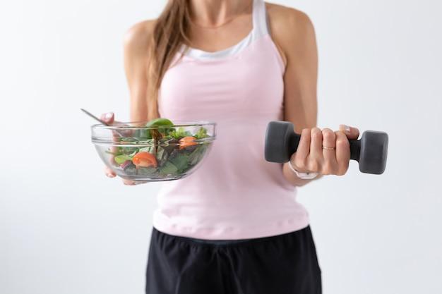 Diät-, lebensmittel- und fitnesskonzept - nahaufnahme von gesundem salat und hantel in weiblicher hand auf weißem hintergrund.