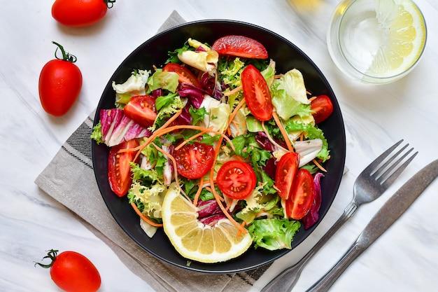 Diät mittagessen frischer gemüsesalat aus tomaten, spinat, salat, zwiebeln und paprika