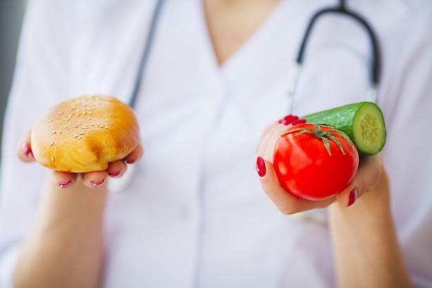 Diät. nahaufnahme auf der doktorfrau, die eine wahl zwischen pastetchen und frischgemüse gibt