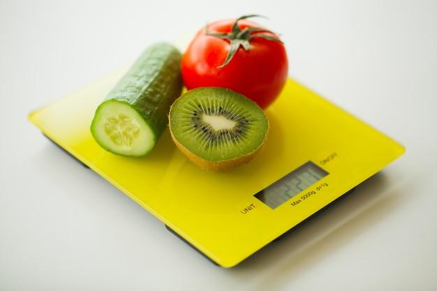 Diät, obst und gemüse auf waage
