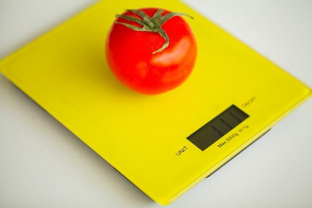 Diät, obst und gemüse mit maßband auf waage