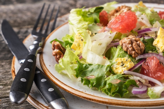 Diät-obstsalat mit garpefruit, käse, salat und walnuss auf einem teller.