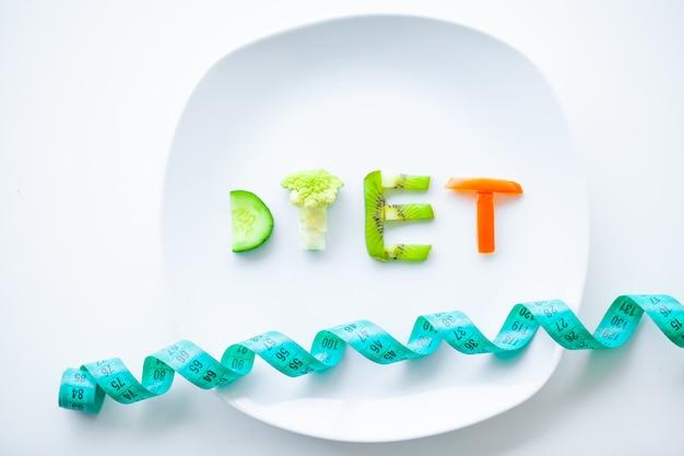Diät oder gewichtskontrolle konzept. schließen sie oben von der platte mit gemüsediät-buchstaben. eignung und gesundes lebensmitteldiät-konzept.