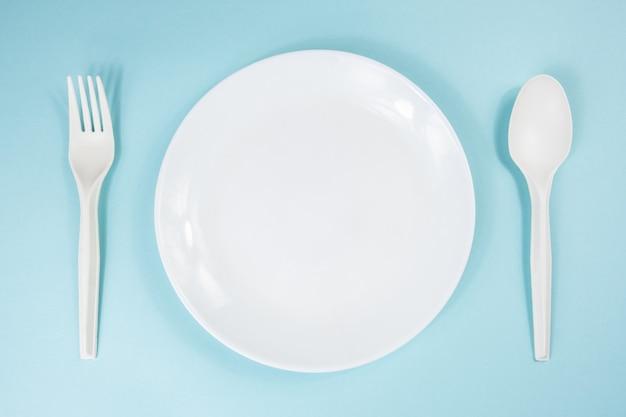 Diät- oder magersuchtkonzept: leere platte auf einer tabelle. draufsicht der leeren schüssel auf hellblauem hintergrund, draufsicht