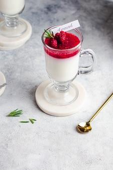 Diät panna cotta mit griechischem joghurt, kokosmilch, himbeergelee, dekoriert mit rosmarin und himbeere im glas. probiotisches konzept. gesundes frühstück. nahansicht