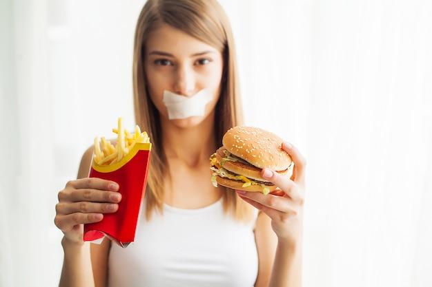 Diät, porträtfrau möchte einen burger essen, aber haftete skochem mund, das konzept der diät, ungesunde fertigkost, willenskraft in der nahrung