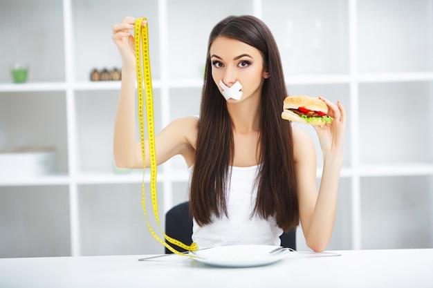 Diät. porträtfrau möchte einen burger essen, aber steckte skochem mund fest, der von der diät, ungesunde fertigkost, willenskraft in der nahrung