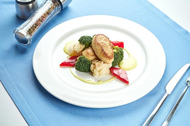 Diät-putenschnitzel, garniert mit gedämpftem gemüse in einem weißen teller auf einer blauen tischdecke.
