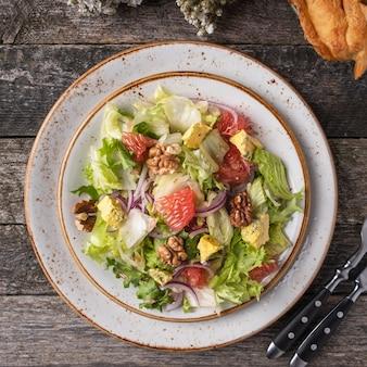 Diät-salat mit garpefruit, käse, salat und walnuss auf einem teller mit gabel und messer