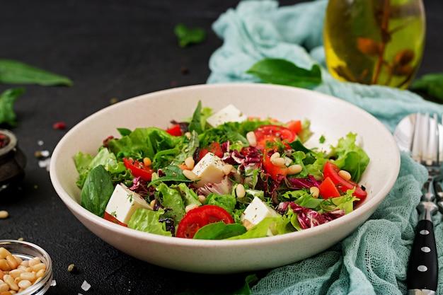 Diät-salat mit tomaten, feta, salat, spinat und pinienkernen.