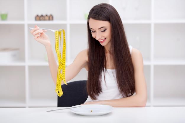 Diät. schöne junge frau, die zwischen früchten und fertigkost wählt