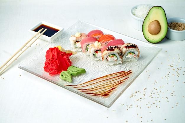 Diät sushi roll regenbogen drache mit frischkäse, thunfisch, aal und lachs auf einem weißen teller in einer zusammensetzung mit zutaten