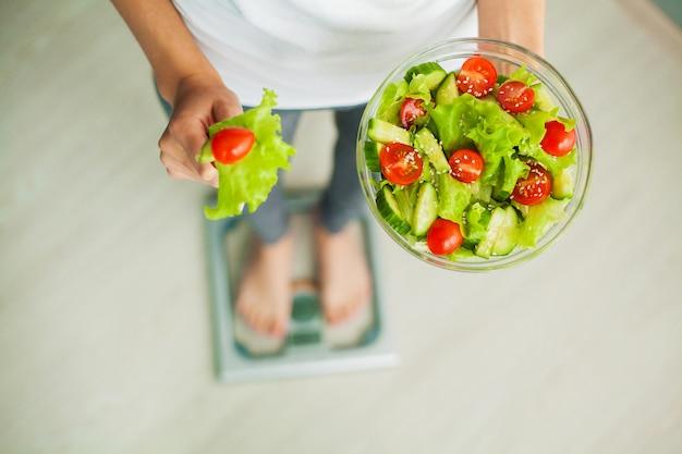 Diät und gesunde ernährung. junge frau, die gesunden salat nach training isst
