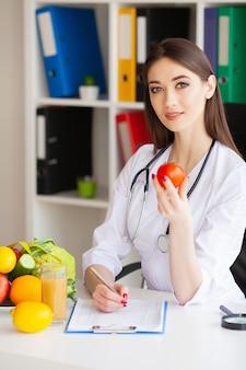 Diät und gesundes konzept. lächelnder ernährungswissenschaftler in ihrem büro