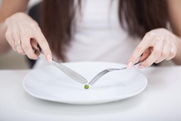Diät, unter magersucht leidend, zugeschnittenes bild des mädchens versuchend, eine erbse auf die gabel zu setzen
