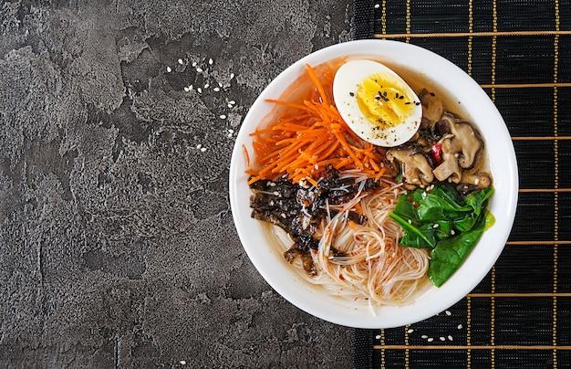 Diät vegetarische schüssel nudelsuppe von shiitake-pilzen, karotten und gekochten eiern. japanisches essen. ansicht von oben. flach liegen
