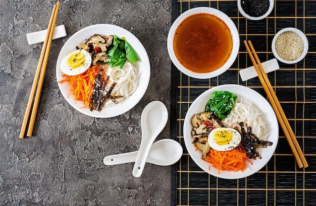 Diät vegetarische schüssel nudelsuppe von shiitake-pilzen, karotten und gekochten eiern. japanisches essen. draufsicht. flach liegen