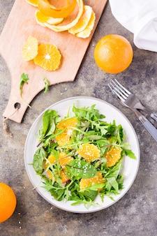 Diät-vegetarischer vitaminsalat aus orangenscheiben und einer mischung aus rucola, mangold und mizun-blättern auf einem teller und einem schneidebrett mit geschälter orange auf dem tisch. ansicht von oben und vertikal