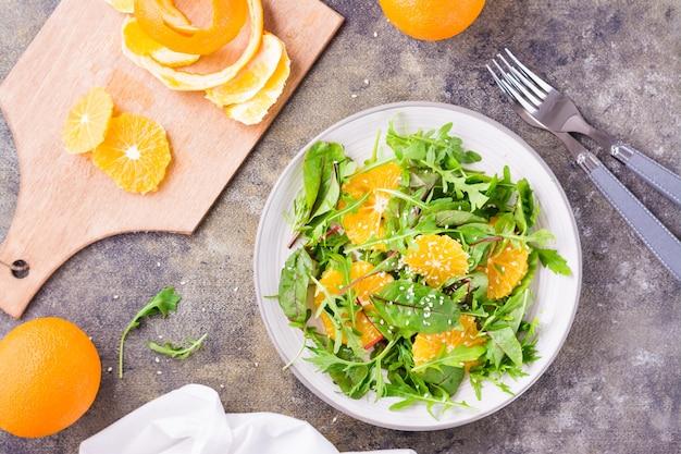 Diät-vegetarischer vitaminsalat aus orangenscheiben und einer mischung aus rucola, mangold und mizun-blättern auf einem teller und einem schneidebrett mit geschälter orange auf dem tisch. ansicht von oben