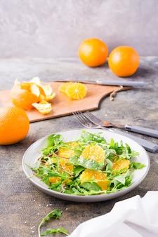 Diät-vegetarischer vitaminsalat aus orangenscheiben und einer mischung aus rucola, mangold und mizun-blättern auf einem teller und einem schneidebrett mit geschälter orange auf dem tisch. vertikale ansicht