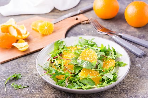 Diät-vegetarischer vitaminsalat aus orangenscheiben und einer mischung aus rucola, mangold und mizunblättern auf einem teller und einem schneidebrett mit geschälter orange auf dem tisch