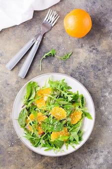Diät-vegetarischer vitaminsalat aus orangenstücken und mischung aus rucola, mangold und mizun-blättern auf einem teller auf dem tisch. ansicht von oben und vertikal
