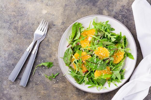 Diät-vegetarischer vitaminsalat aus orangenstücken und mischung aus rucola, mangold und mizun-blättern auf einem teller auf dem tisch. ansicht von oben