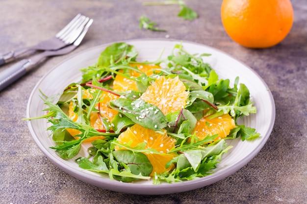 Diät-vegetarischer vitaminsalat aus orangenstücken und mischung aus rucola, mangold und mizun-blättern auf einem teller auf dem tisch. nahansicht