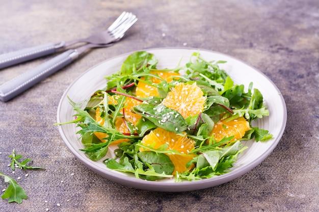 Diät-vegetarischer vitaminsalat aus orangenstücken und mischung aus rucola, mangold und mizun-blättern auf einem teller auf dem tisch