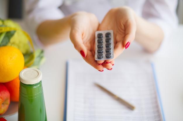 Diät. weiblicher ernährungswissenschaftler holding blisters of pills