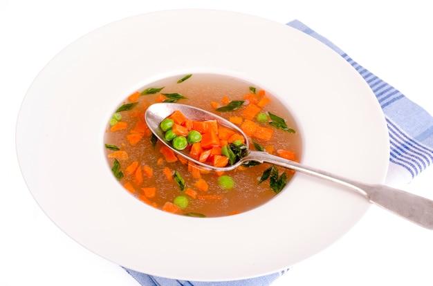 Diätetische gemüsesuppe mit karotten, erbsen und frühlingszwiebeln.