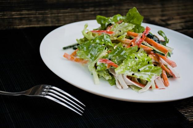 Diätetische lebensmittel, frischer gemüsesalat mit krabbenstäbchenimitat, gewürzt mit sojasauce und japanischem sesam. in streifen schneiden.