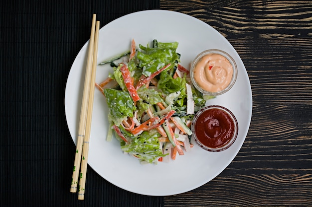 Diätetische lebensmittel, frischer gemüsesalat mit krabbenstäbchenimitat, gewürzt mit sojasauce und japanischem sesam.