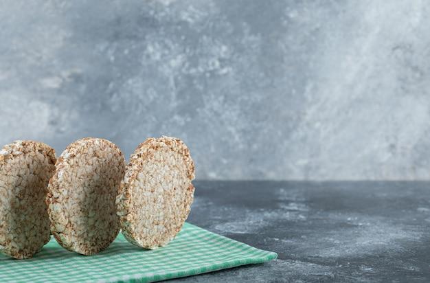 Diätetische runde reiskuchen auf gestreifter tischdecke.