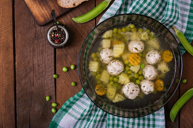 Diätetische suppe mit hühnerfleischbällchen und grünen erbsen in einer glasschüssel auf einem holztisch. draufsicht