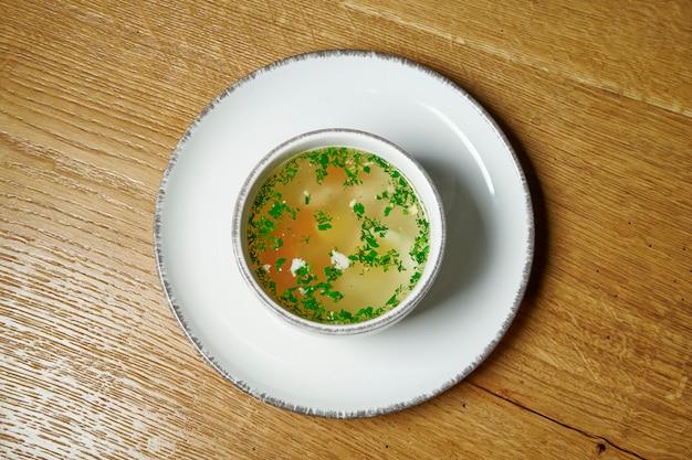 Diätetische suppe mit huhn, gemüse und petersilie auf holztisch in weißer schüssel. draufsicht leckere suppe. flaches essen