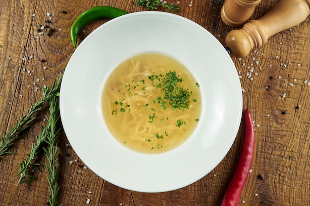Diätetische suppe mit huhn, gemüse und petersilie in kompostion mit zutaten auf holzoberfläche in weißer schüssel. draufsicht leckere suppe. flaches essen