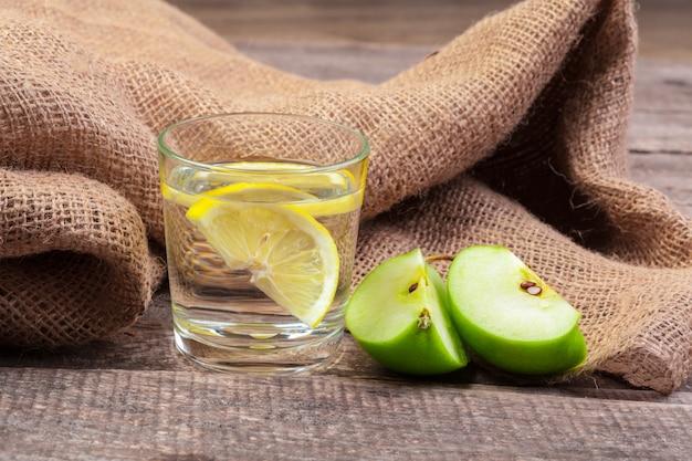 Diätetisches detoxgetränk mit apfelscheiben im trinkwasser und einem frischen apfel auf einem holztisch, abschluss oben