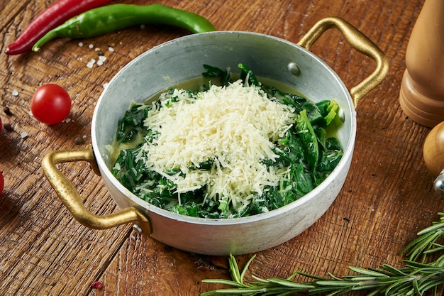Diätetisches essen - gedünsteter spinat in einer cremigen knoblauchsauce mit parmesan in einer dekorativen pfanne auf holzoberfläche in komposition mit gewürzen