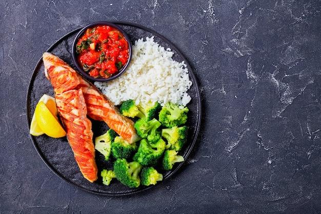 Diätetisches fischgericht: gegrilltes lachsfilet mit gekochtem brokkoli und reis mit tomaten-spinat-mischung