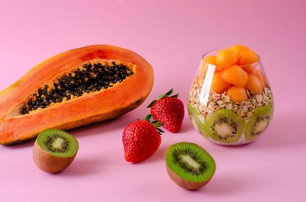 Diätfrühstück mit frischer papaya, erdbeeren, kiwi, haferflocken und chia-pudding