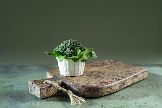 Diätkleiner kuchen vom brokkoli- und maissalat auf hölzernem brett