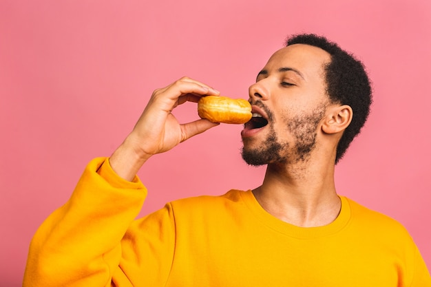 Diätkonzept. hungriger bärtiger mann, der donuts auf rosa isoliert isst.