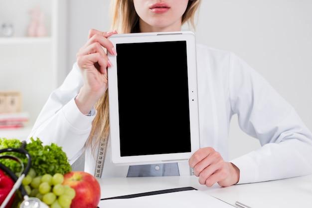 Diätkonzept mit dem weiblichen wissenschaftler, der tablettenschablone zeigt